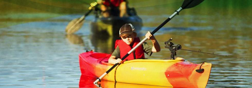 Boy paddling kayak on lake