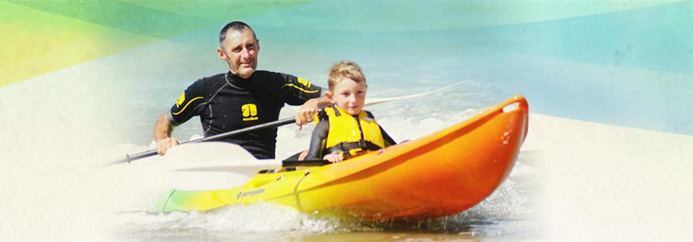 Father and son paddling at the beach
