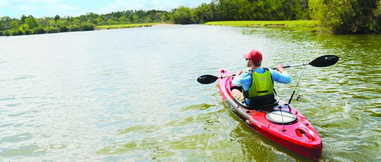 Man paddling a red Swifty Kayak